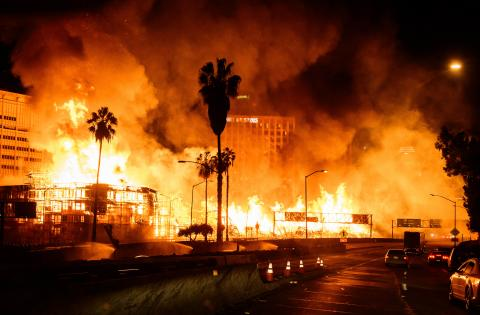 Huge flames extending from wood construction site near Los Angeles freeway.