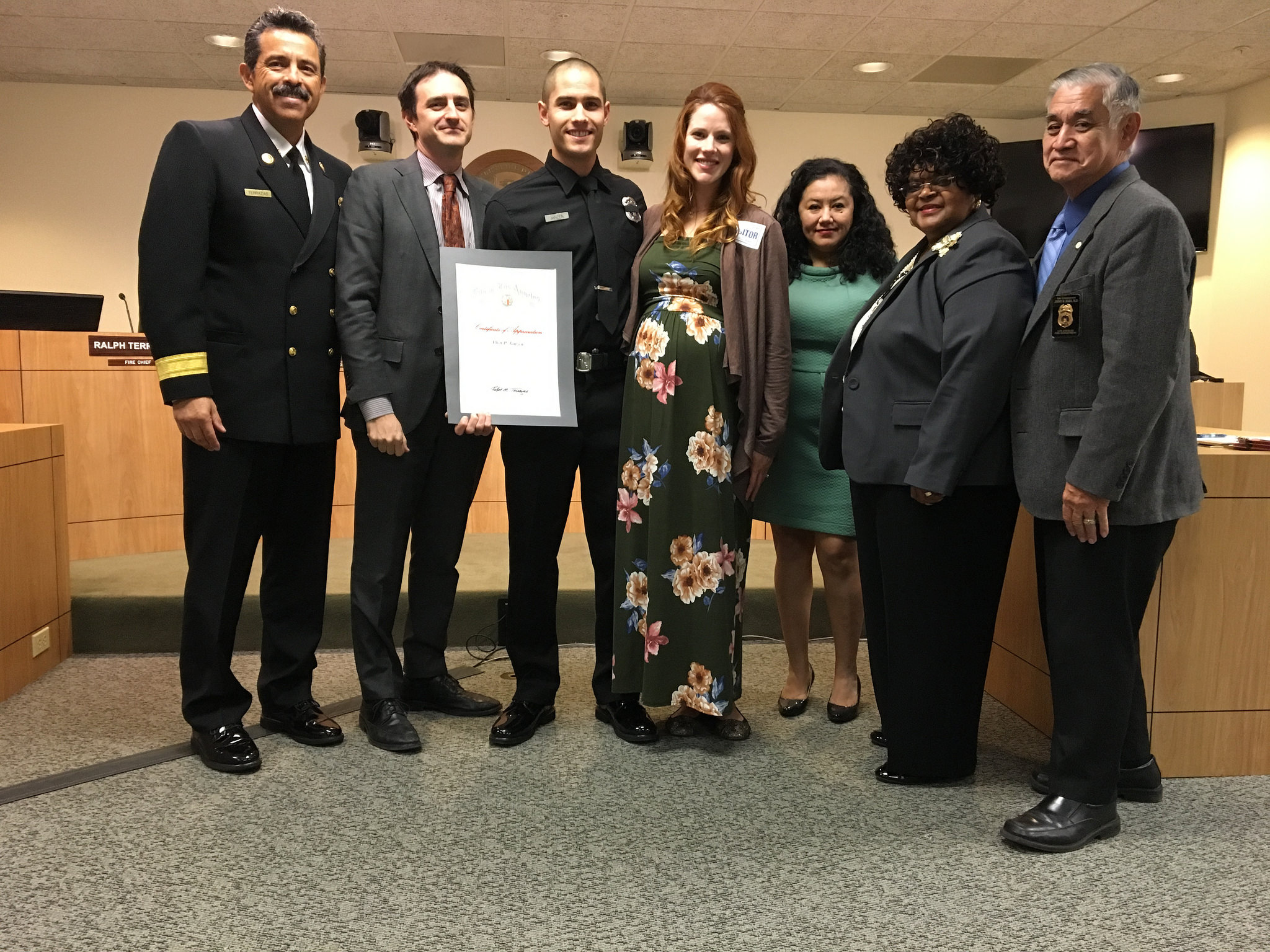 Image of Firefighter awardee standing with with wife, Fire Chief and members of the Board of Fire Commissioners