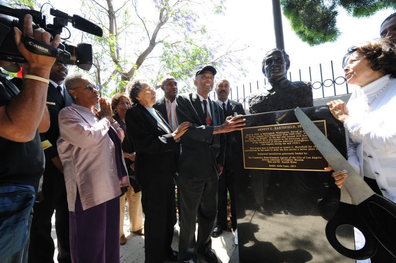 Arnett Hartsfield, Jr. smiling during dedication of bronze statue surrounded by supporters