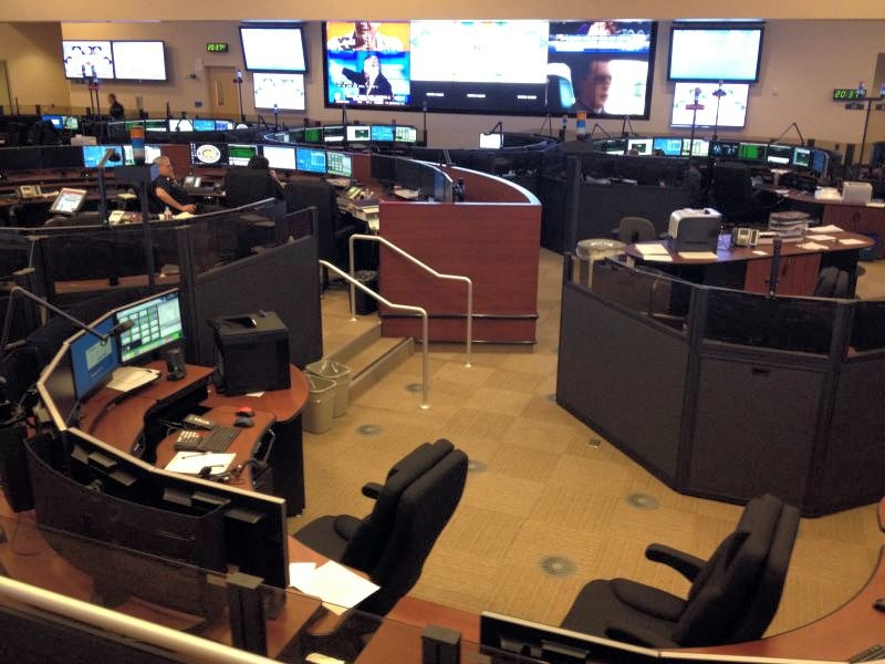 LAFD's Dispatch center. Multiple desks in a rounded configuration with multiple monitors.