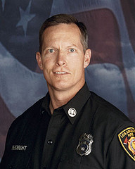 Head shot of Captain McKnight, a white male in uniform with the American Flag behind him.