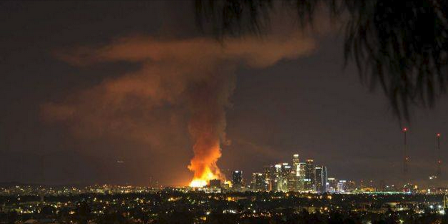 Distant view of Los Angeles skyline with very large fire visible.