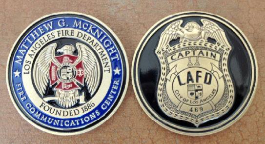 Challenge coin with the new custom logo of the Communications Center on one side with a replica of Captain McKnight's badge on the opposite side of the coin.