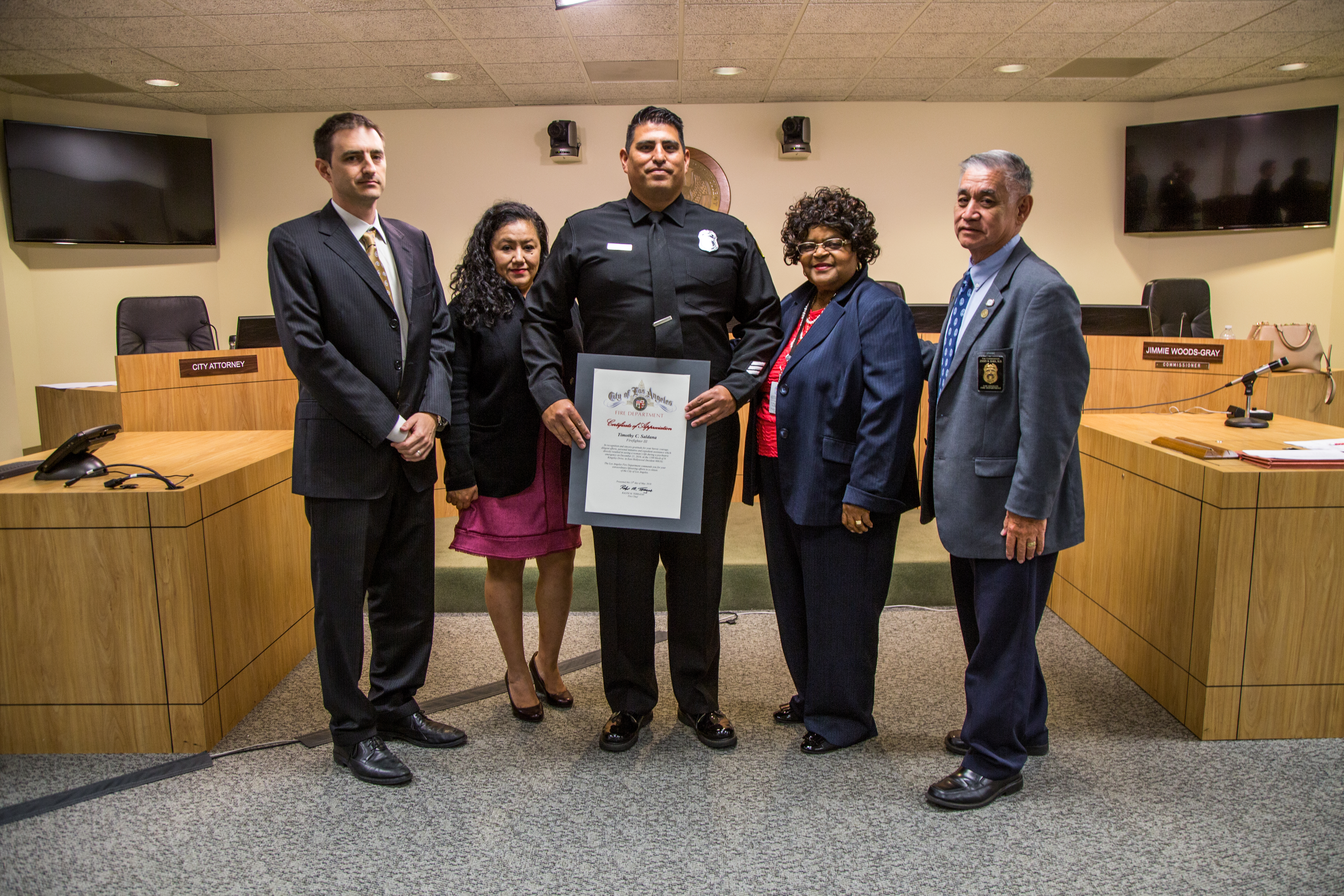 LAFD Firefighter Saldana stands with Fire Commissioners with a Certificate of Appreciation