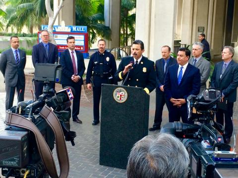Fire Chief Terrazas speaking at a lectern to the news media.