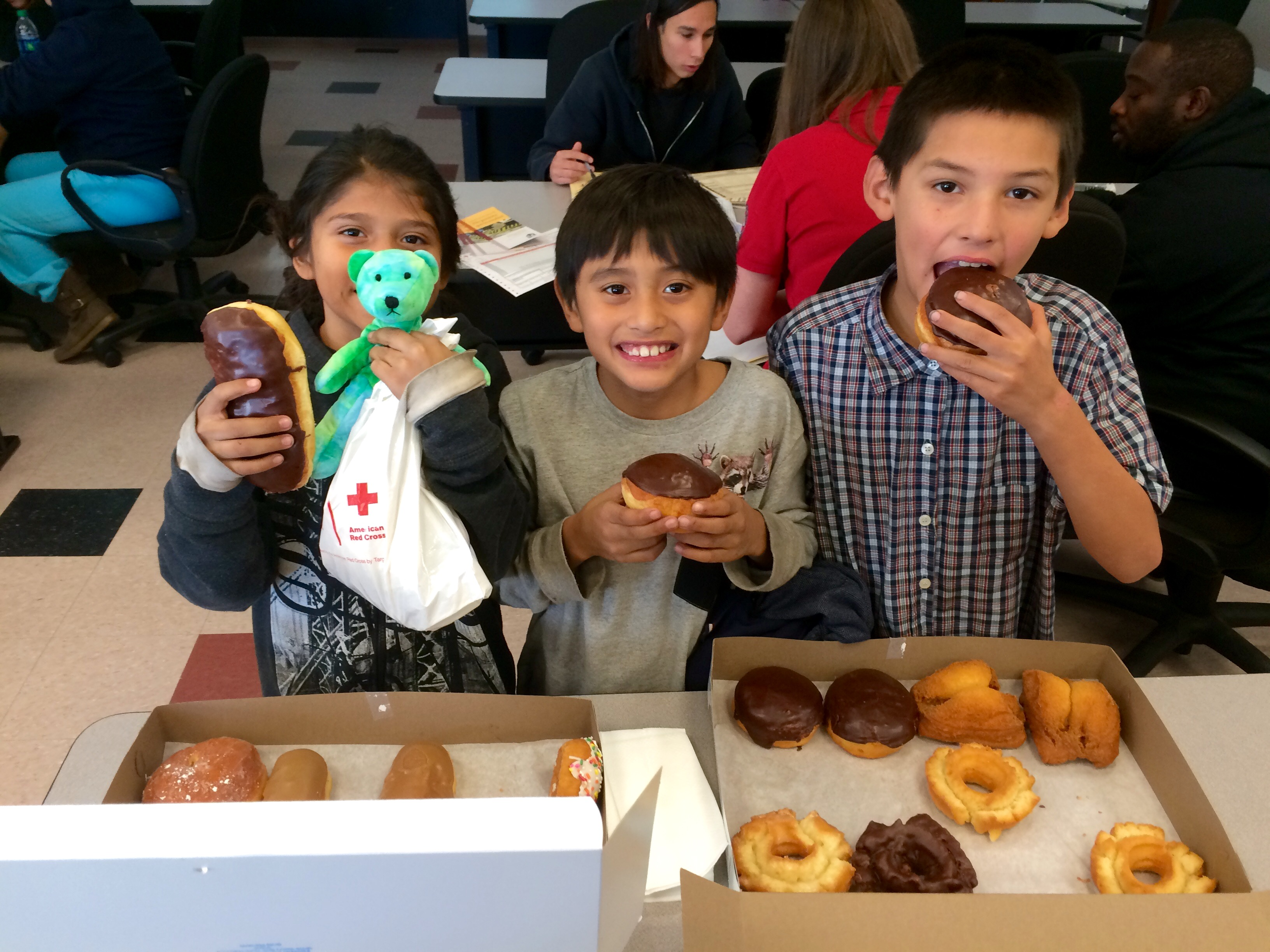 Three smiling children while eating donuts.