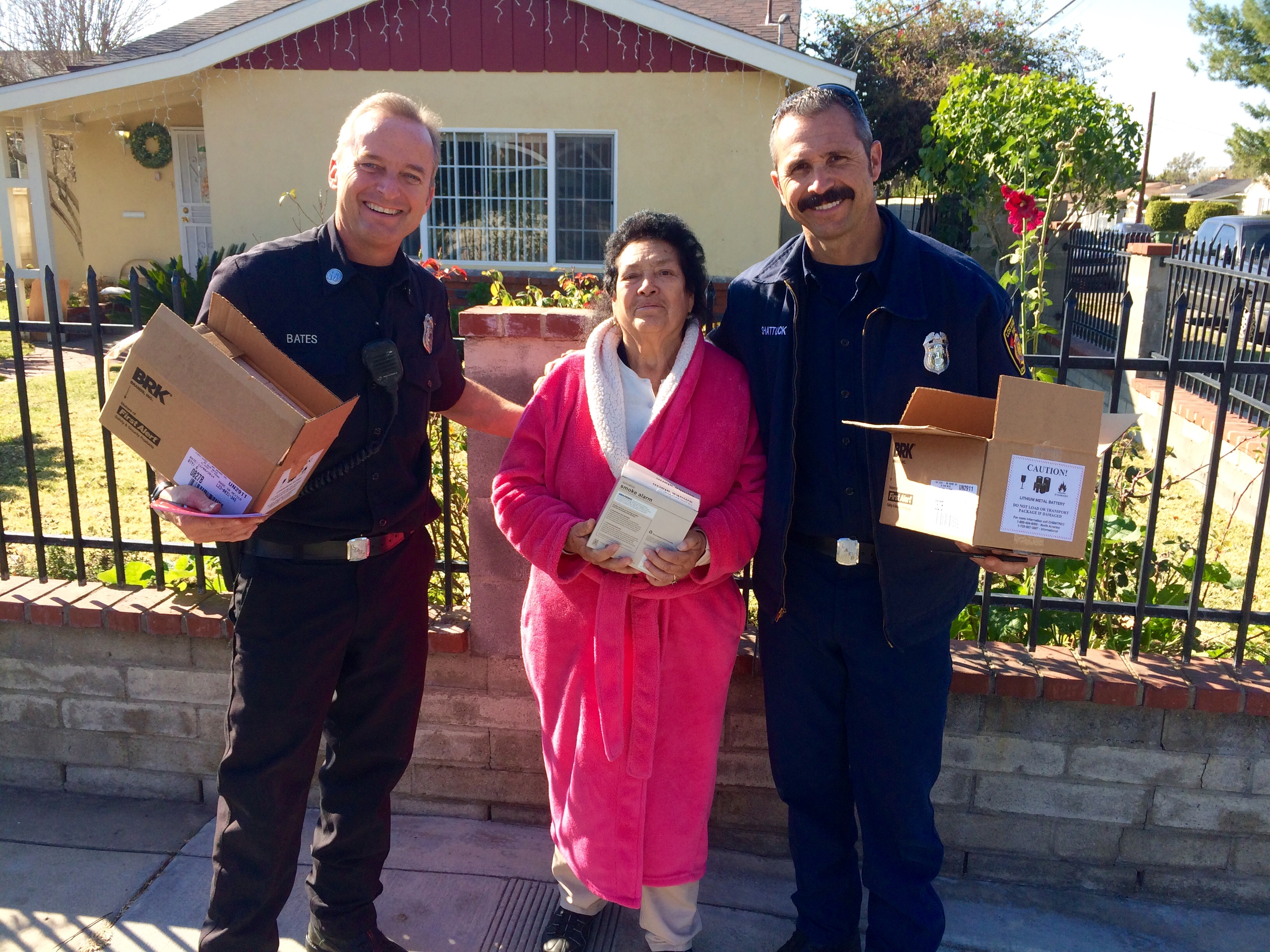 2 firefighters smiling while providing free smoke alarms to a resident.