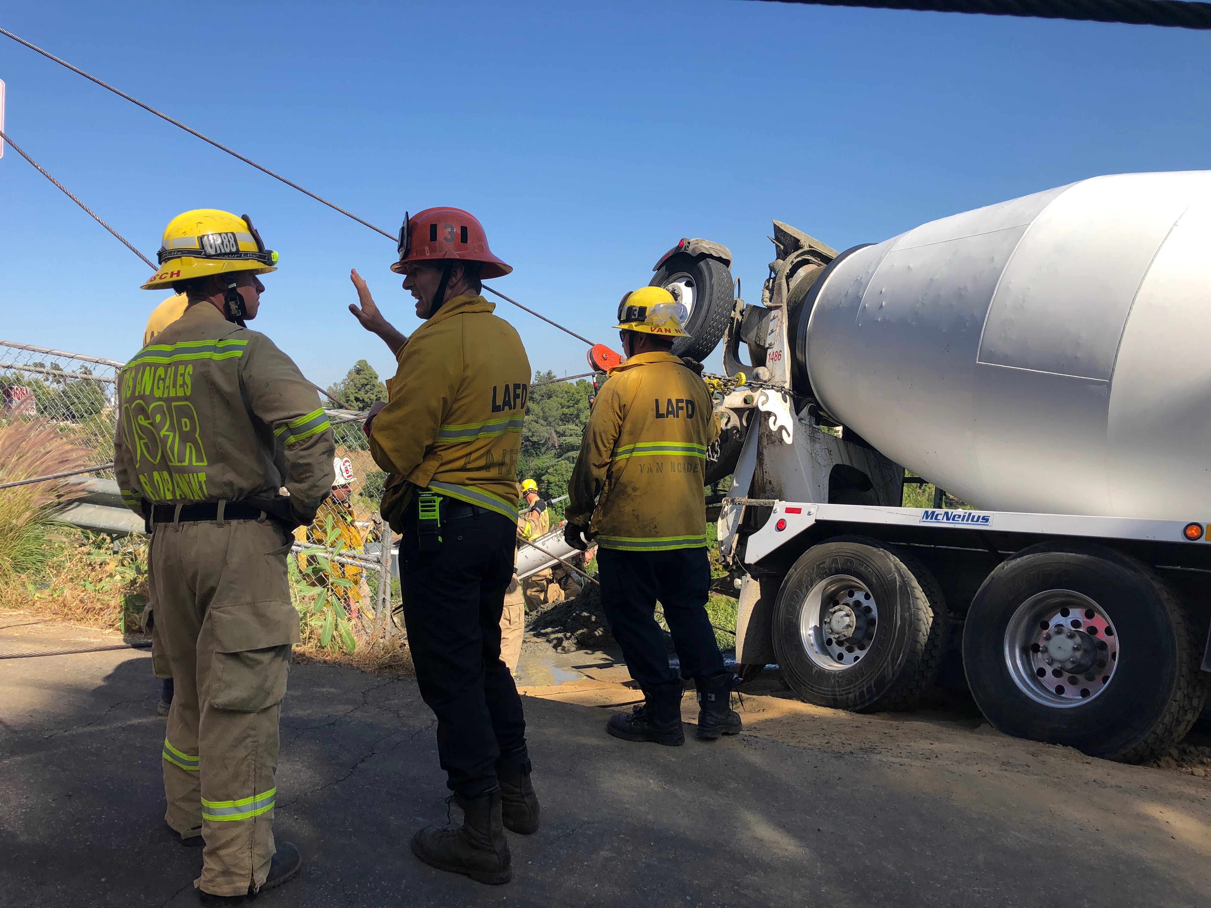 Rigging shown leading to the mixer truck with firefighters in the foreground