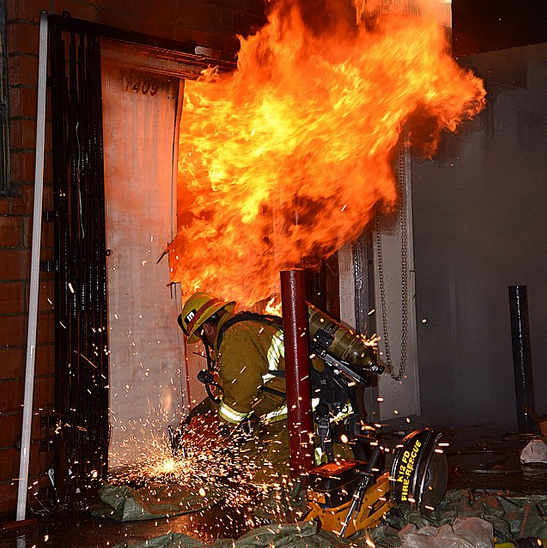 A firefighter crouched using a rotary saw to force entry into a burning structure.