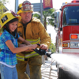 A firefighter teaches a young girl how to use a fire hose