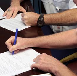 People signing paperwork