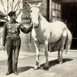 A historic photo from the LAFD archives of a firefighter and his horse