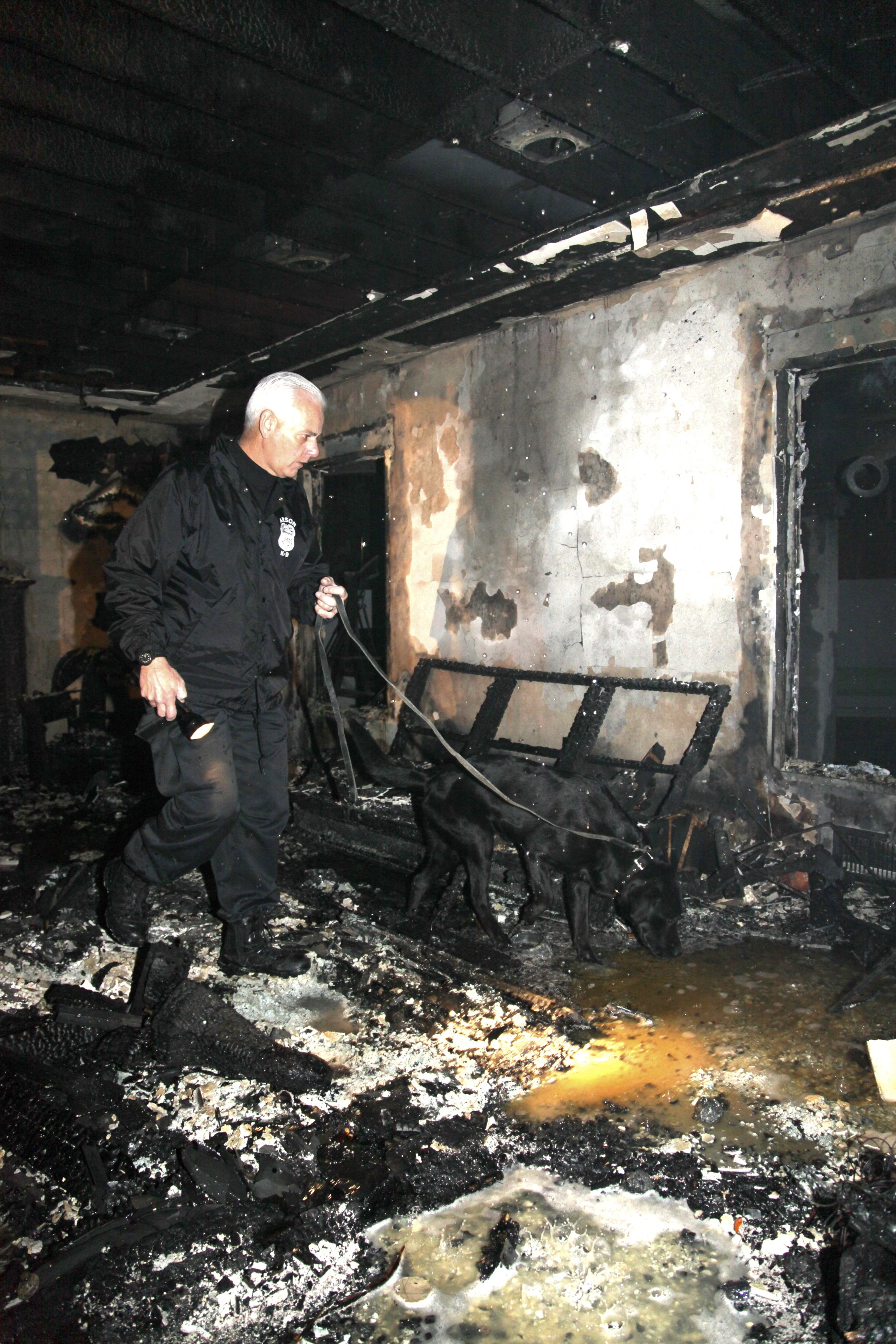 Major and his handler examine the charred remains inside an ash and charcoal filled room, after a structure fire.