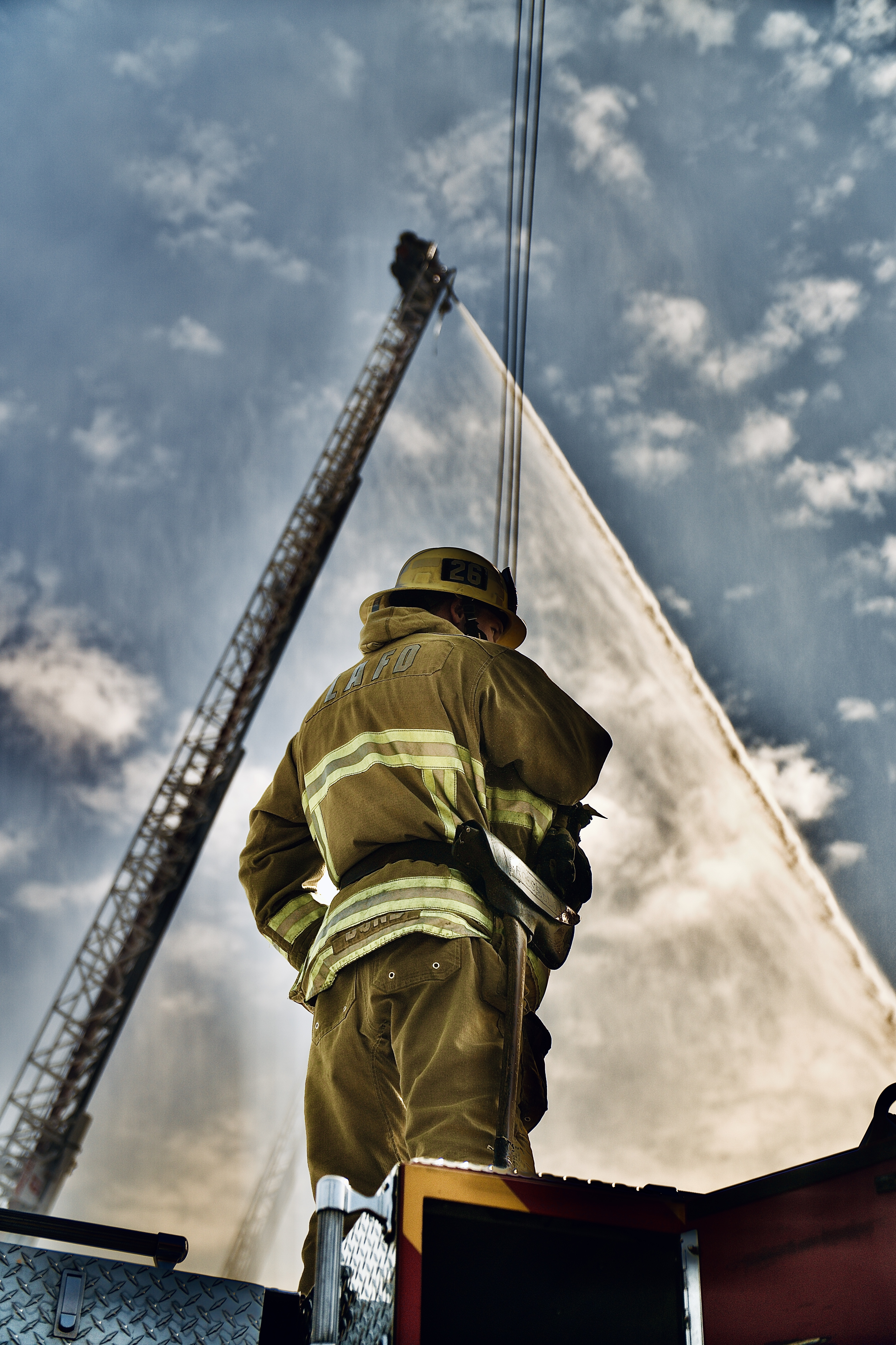 Firefighter standing on fire truck with aerial ladder in the background