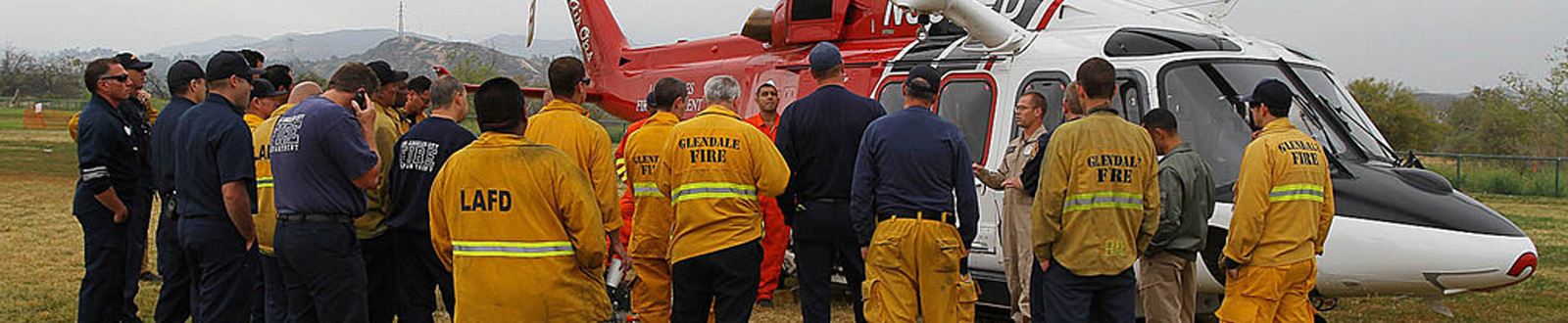 An LAFD team meet in front of an LAFD helicopter