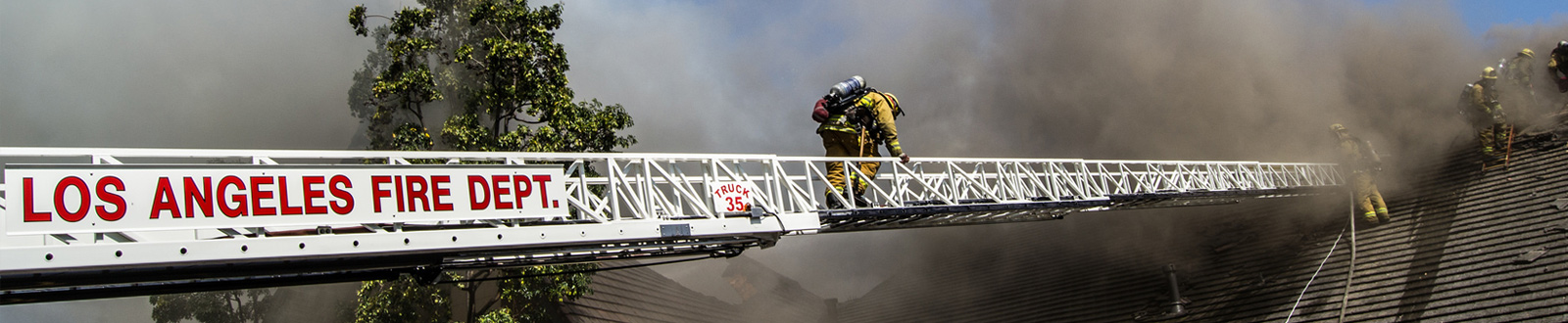 A firefighter walks across a large ladder to a roof of a burning house