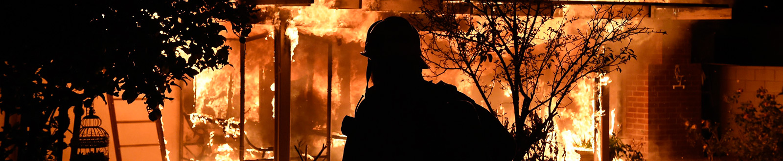 A firefighter silhouetted by a burning house