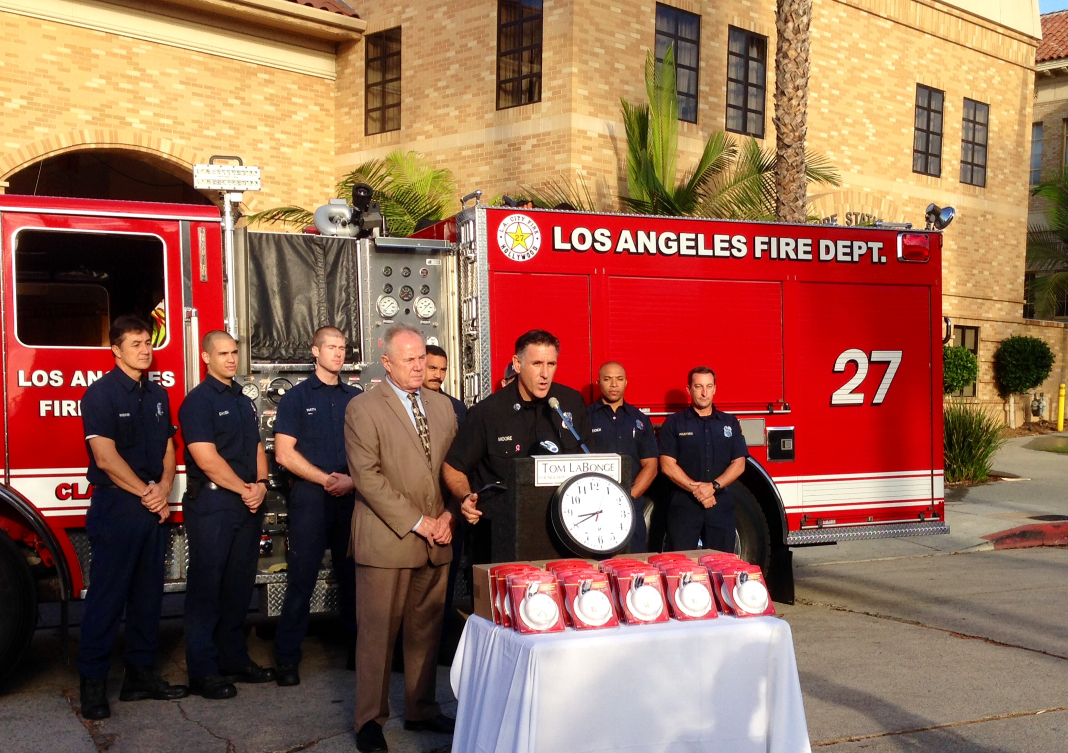 LAFD Captain Moore speaking at lectern. Firefighters and a fire engine in the background and a table of smoke alarms in the foreground.
