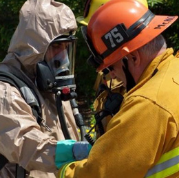 One firefighter helps another into his hazmat gear