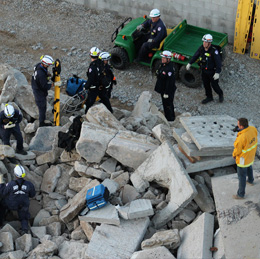 homeland security team works in a pile of rubble