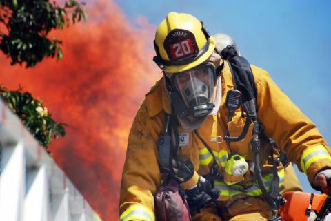 Firefighter looking directly into camera as descending aerial ladder with fire behind him