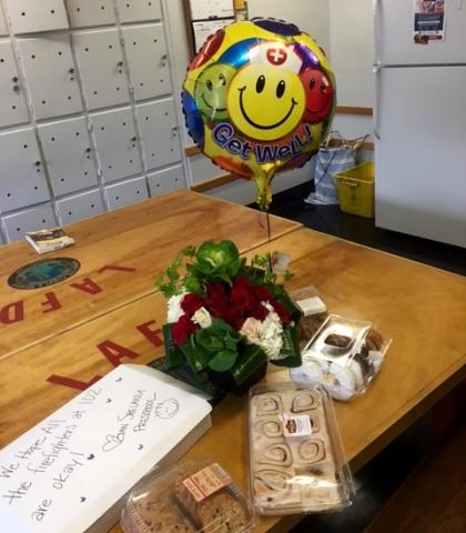 """Balloon and assortment of """"goodies"""" on the fire station kitchen table."""