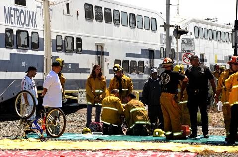 Firefighters and passengers in front of train.