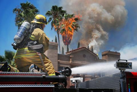 Firefighter on top of engine operating the wagon battery.  Large palm tree ablaze in front of structure