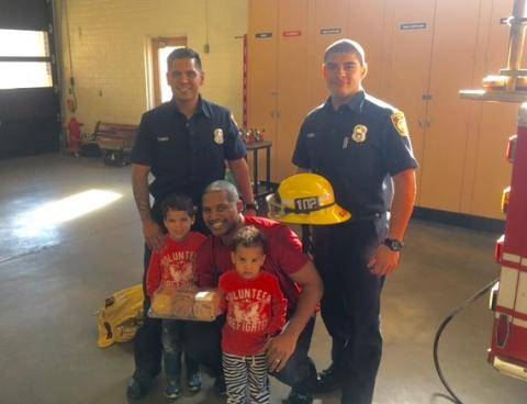 Firefighters and a family at fire station 102.