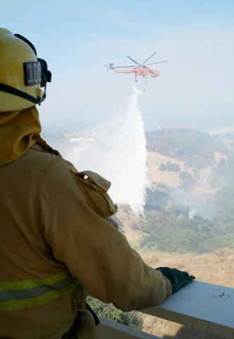 Firefighter watches helitanker in distance make water drops.