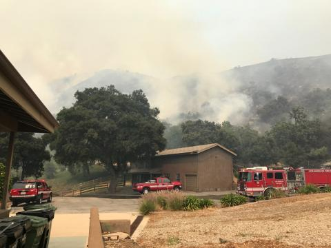 Fire engines defending home against approaching brush fire