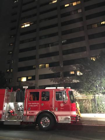 Image of fire engine in front of large, high rise apartment building