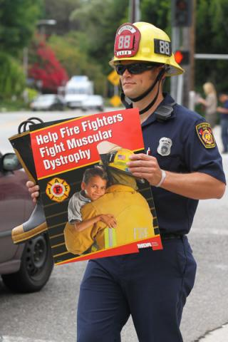 Firefighter with sign raising money for MDA Fill the Boot