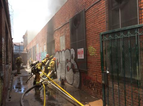 Looking down alley next to building, firefighters working to make entry and setting up hose lines