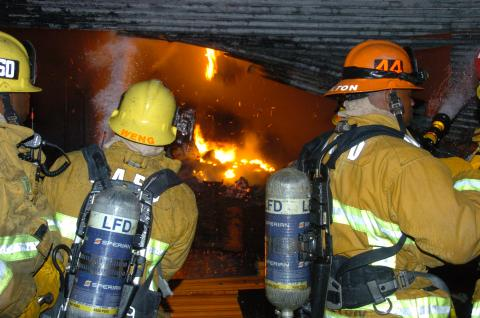 three firefighters in front of a rolling steel door cut open to show fire