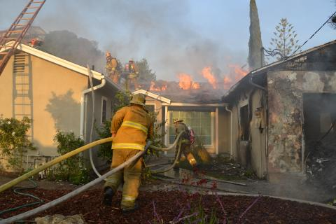Firefighters Advance Hoselines on Burning Home in Sun Valley