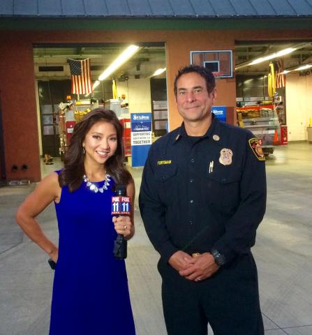 LAFD Battalion Chief in front of Station 64 with news reporter.