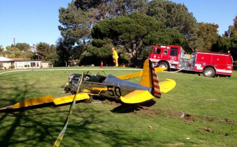 Small single engine yellow plane on golf course grass.
