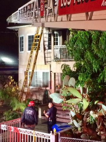 Image of house with fire truck ladder extended at the top, wood ladder to the window and Arson Investigator talking with LAPD officer