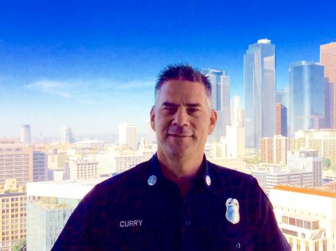 Headshot of Captain Curry in uniform with the Los Angeles skyline in background.