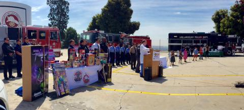 Press Conference with fireworks display in front and fire engines in the background.