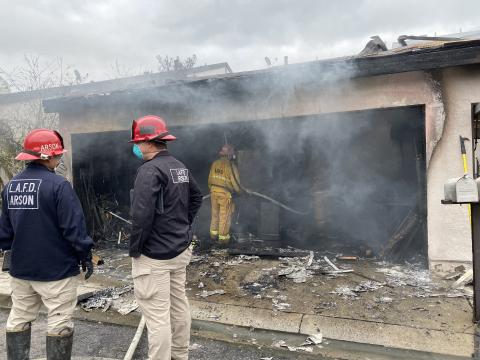 Two arson inspectors standing in front of a burned out garage with a firefighter inside holding a hose line