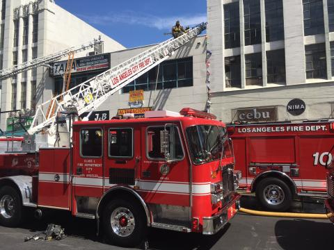 Fire engines in front of building with ladders to roof