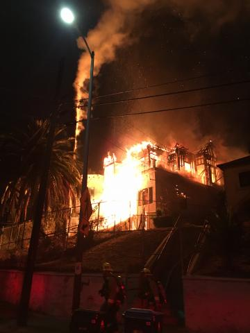 Image shows large Victorian style home fully engulfed in flames