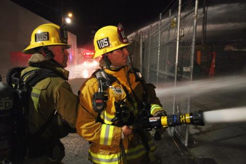 Two firefighters spraying water.