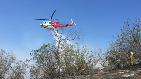 Helicopter making water drop over brush fire