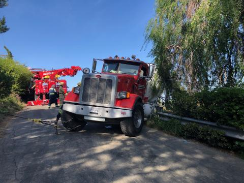 Concrete mixer truck shown at edge of embankment with fire truck rescue rig in the background