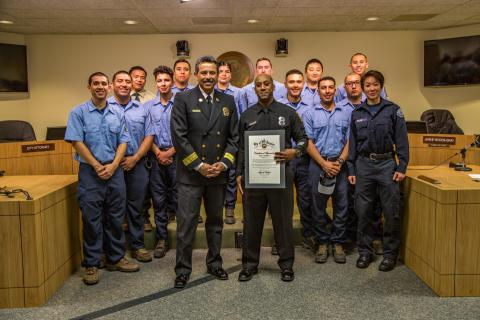 Los Angeles Firefighter Paul Wingate (holding certificate) stands alongside Fire Chief Ralph Terrazas and the volunteer members of LAFD Crew 3.