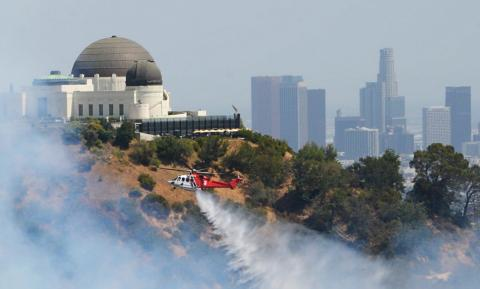A Los Angeles Fire Department helicopter drops water on a wildfire near the Griffith Observatory on July 10, 2018.