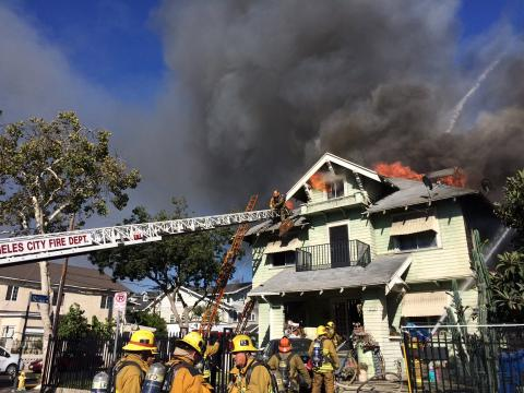 Large craftsman style home with heavy fire and firefighters climbing ladder